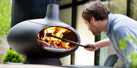 A photo of a man stoking the burning wood in a Morsø Forno Outdoor Oven